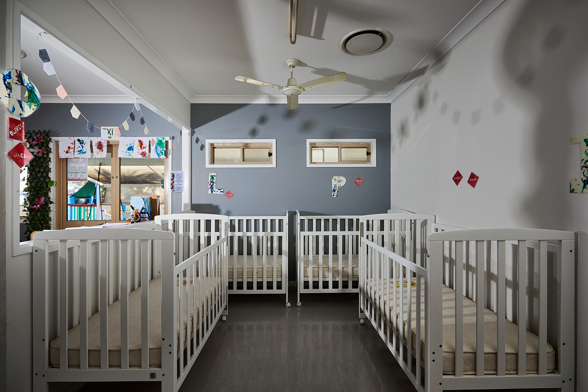 A nursery room with 4 baby cots in view